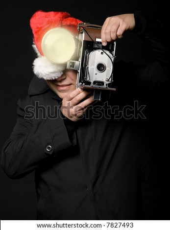 Photographer wearing santa hat taking a picture with vintage camera and flash - stock photo