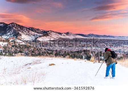 Photographer with a tripod during the winter a sunrise near Boulder, Colorado in the mountains. - stock photo