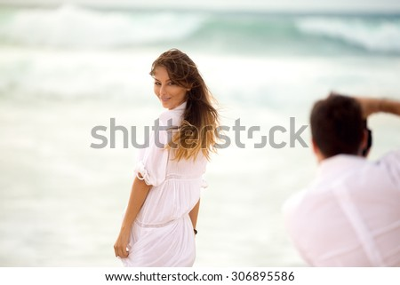 photographer with camera taking picture of young beautiful woman on the beach - stock photo