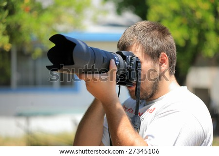 Photographer with professional camera and telephoto lens shooting outdoors. Shallow DOF. - stock photo
