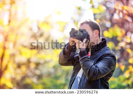 photographer with professional digital camera taking pictures in nature - stock photo