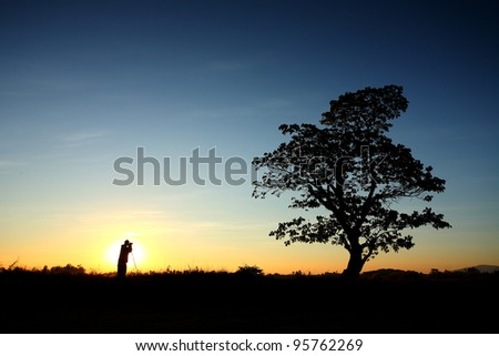 Photographer with tree in rural dawn at North, Thailand - stock photo