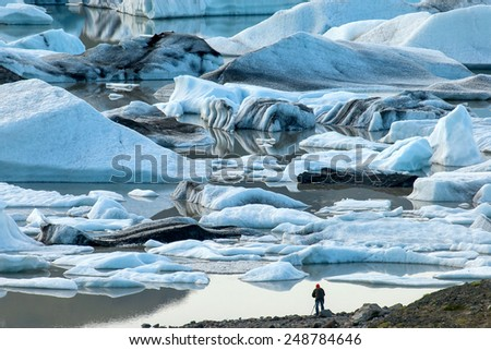 Photographer with tripod in a glacier lagoon in Iceland - stock photo
