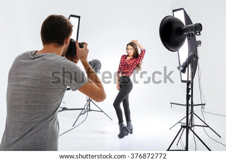 Photographer working with model in equipped studio - stock photo
