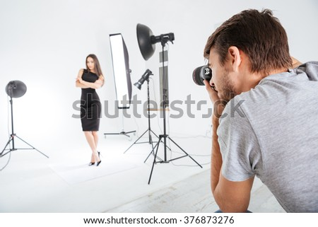 Photographer working with model in studio with softboxes - stock photo