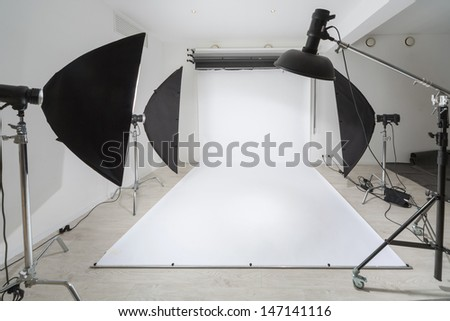 Photographic equipment and a white backdrop in studio. - stock photo