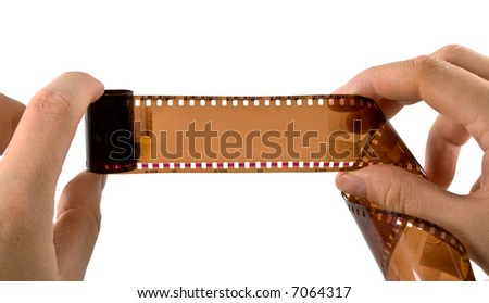 Photographic film in hands. Isolated on white - stock photo