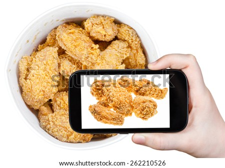 photographing food concept - tourist takes picture of hot fried chicken wings in basket on smartphone, USA - stock photo