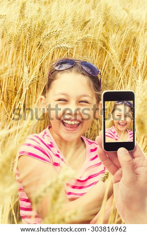 Photographing phone kid in wheat - stock photo