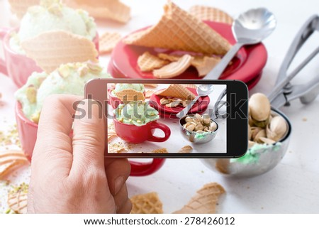 Photographing pistachios ice cream with cellphone camera,selective focus - stock photo