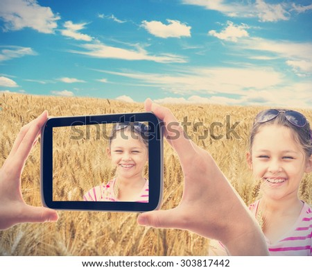 photographing smartphone kid in a wheat field - stock photo