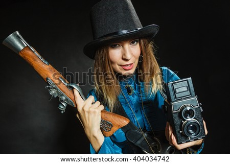 Photography and retro style. Young vintage attractive girl holds old aged camera. Steampunk photographer with gun pistol. - stock photo