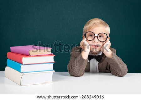 Photography. Cheerful smiling little boy sitting at the table. Looking at camera School concept - stock photo