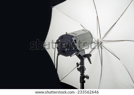 Photography Studio Flash Head with Umbrella and dark black copy space. - stock photo