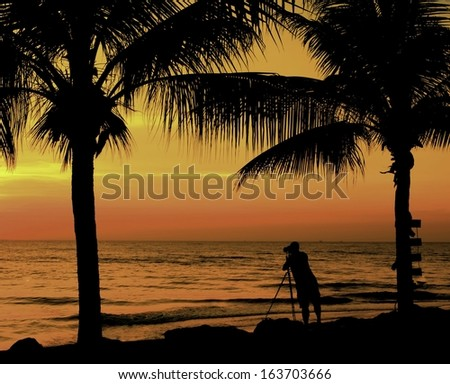 Photogrpher working at sunrise on the beach. - stock photo