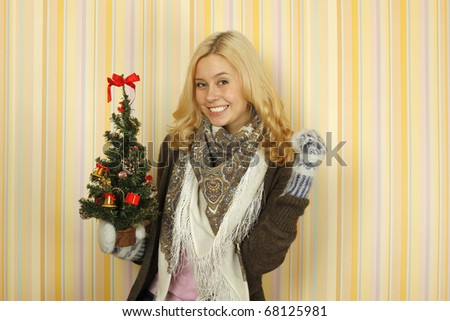 Photos of a beautiful young woman in mild winter mittens, scarves and knit sweaters. Happy and holding a small Christmas tree - stock photo