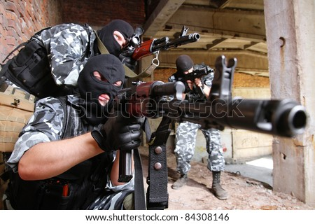 Photos of heavy equipped soldiers or terrorists in black masks with automatic guns.