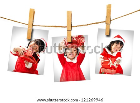 Photos of little girl wearing Santa Claus hat  hanging on white background. - stock photo