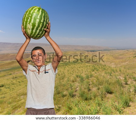 Photos of Tajik young men with a huge watermelon (weight 40 kg) on the background of the valley of Khatlon