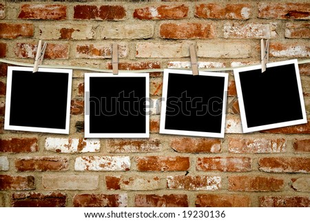 Photos on a clothes line against a grungy brick wall - stock photo