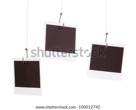 Photos on fish hooks isolated on white - stock photo