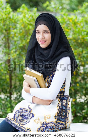 Photos portrait  outdoors beautiful woman dressed in Islamic hijab carries a book in hand, and a cute smile sitting on a green background of natural tree.