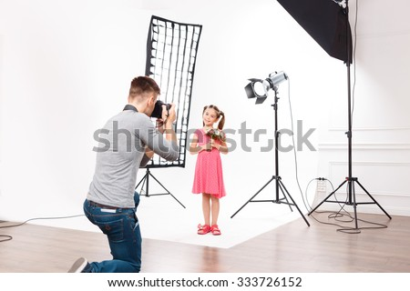 Photoshoot in progress. Young handsome male photographer in the process of taking photos of small model girl. - stock photo
