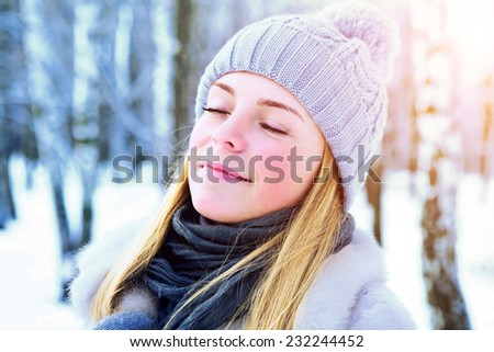 Photoshoot in the winter in snow-covered park. The young beautiful girl with ideal skin poses - stock photo