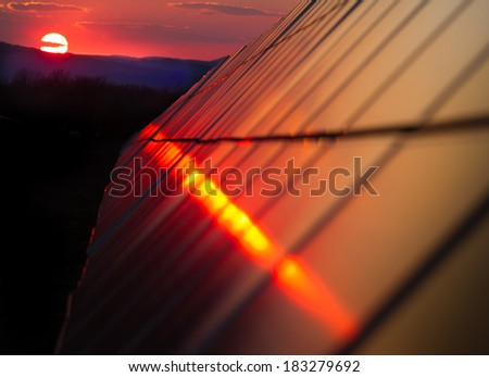 Photovoltaic modules on the background of a sunset - stock photo