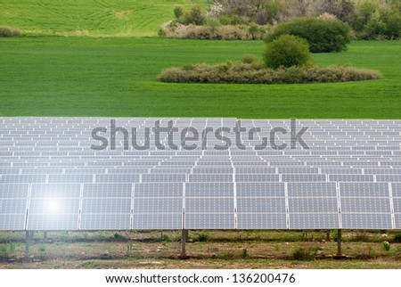 Photovoltaic (PV) solar cells with sunlight reflection in green field generation clean electricity. - stock photo