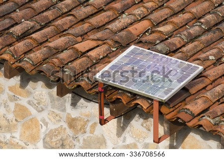 Photovoltaic Solar Panels on old house, best cheap and environment energy, with euro coins and money bills, in the cells  - stock photo
