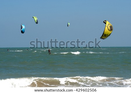 PHRACHUAP KHIRI KHUN,THAILAND-DECEMBER 20,2013 : Kite surfers in  the sky of Phranburi sea near Phranburi District. Kite surfing is a popular water sport in Phrachuap Khiri Khun Province,Thailand. - stock photo
