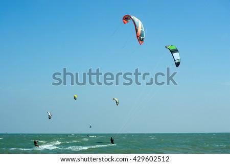 PHRACHUAP KHIRI KHUN,THAILAND-DECEMBER 20,2013 : Kite surfers in  the sky of Phranburi sea near Phranburi District. Kite surfing is a popular water sport in Phrachuap Khiri Khun Province,Thailand. - stock photo