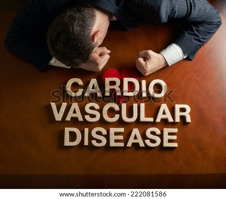 Phrase Cardio Vascular Disease made of wooden block letters and devastated caucasian man in a black suit sitting at the table with the red symbolic heart, top view composition with dramatic lighting - stock photo