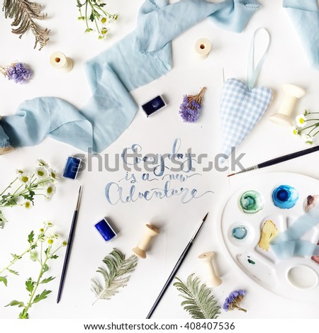 """Phrase """"every day is a new adventure"""" written in calligraphy style on paper with chamomile, blue ribbon, paint brush, palette, handmade heart, branches and spool. Flat lay, top view - stock photo"""