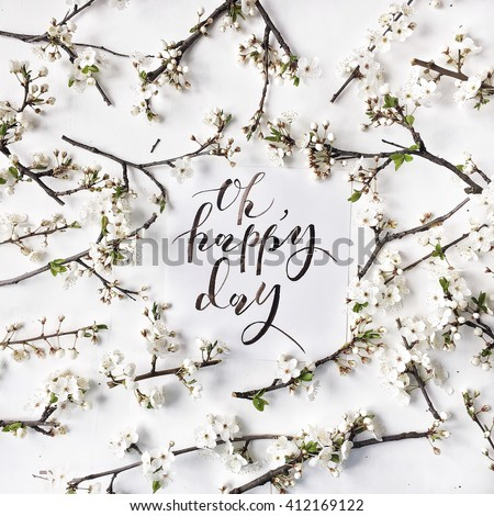 "Phrase ""oh happy day"" written in calligraphy style on paper with wreath frame with white flowers and branches isolated on white background. flat lay, overhead view, top view - stock photo"