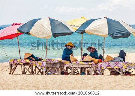 PHU QUOC, VIETNAM - APRIL 21, 2014: Beach masseuses resting  waiting of tourists in the shade of umbrellas at Long beach on Phu Quoc island, Vietnam.  - stock photo