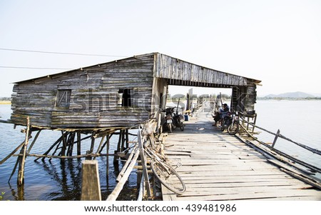 Phu Yen, Vietnam - Mar 31, 2016: Ong Cop bridge ( Mr Tiger 's wooden bridge), the longest wooden bridge in Vietnam. A woman cycling on the bridge