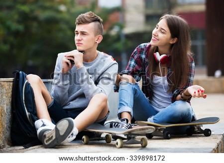 Phubbing: teenager and friend asking for attention in the city - stock photo