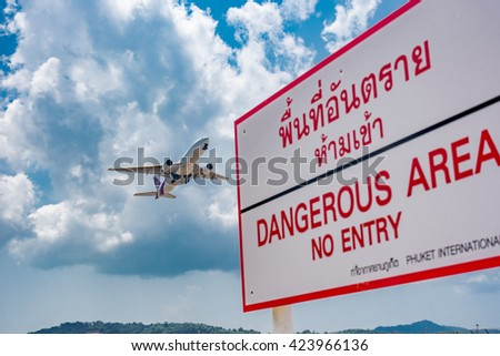Phuket - Thailand -  April 24,2016 :Thai airways airplane  taked off with  warning signage at Phuket airport over  Mai Khao beach in Thailand.