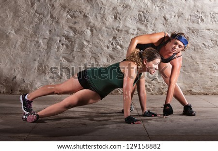 Physical fitness trainer with woman doing right angle pushups - stock photo