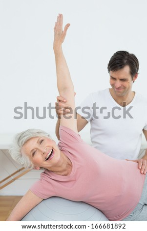 Physical therapist assisting senior woman with yoga ball in the gym at hospital - stock photo