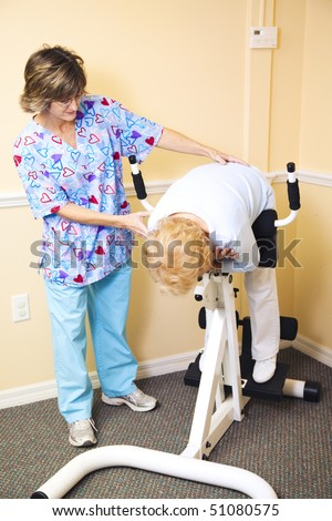 Physical therapist at the chiropractors office, helping a senior woman stretch her spine. - stock photo