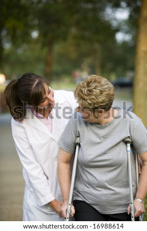 physical therapist helping a woman on crutches - stock photo