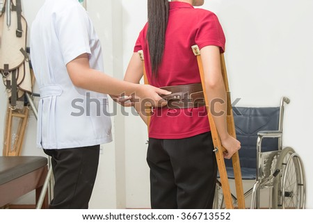 Physical therapist helping patient to walk using crutches  in hospital, physical rehabilitation therapy - stock photo