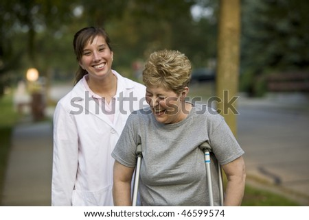 Physical therapist laughs with a patient - stock photo