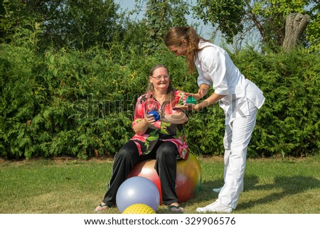 Physical Therapist Showing Exercise With Spiky Balls For Senior Woman Sitting On A Gym Ball