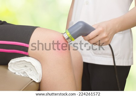 Physical therapist using ultrasound probe on woman patient 's knee for release pain - stock photo