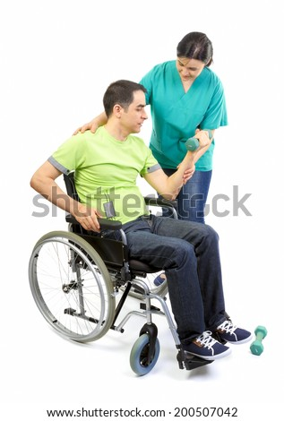 Physical therapist works with patient in lifting hands weights. Young adult in wheelchair. - stock photo