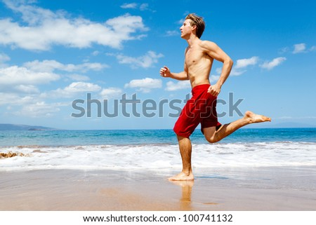 Physically fit man running on Beach - stock photo